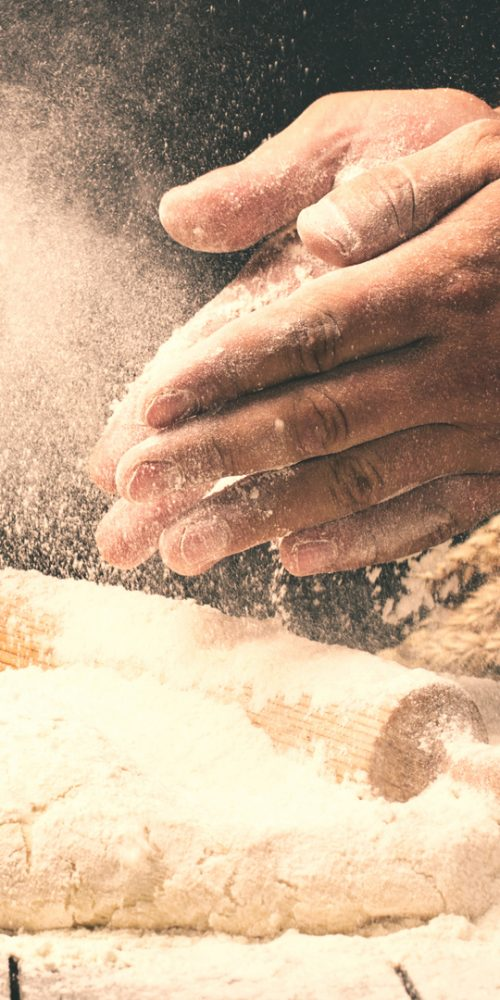 Man preparing bread dough on wooden table in a bakery close up